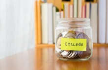 Many world coins in saving money jar with college label on jar, concept to financial planning for kids