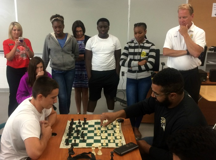 Baltimore Ravens lineman John Urschel plays chess with Dundalk High student.
