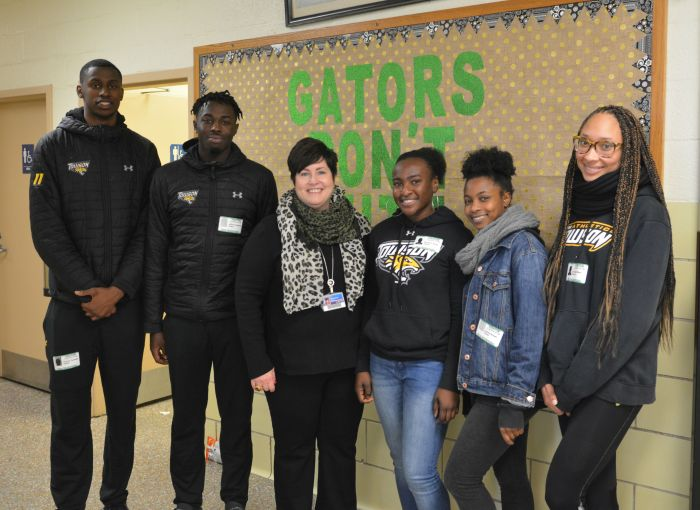 Towson University student athletes photographed with Perry Hall Elementary principal